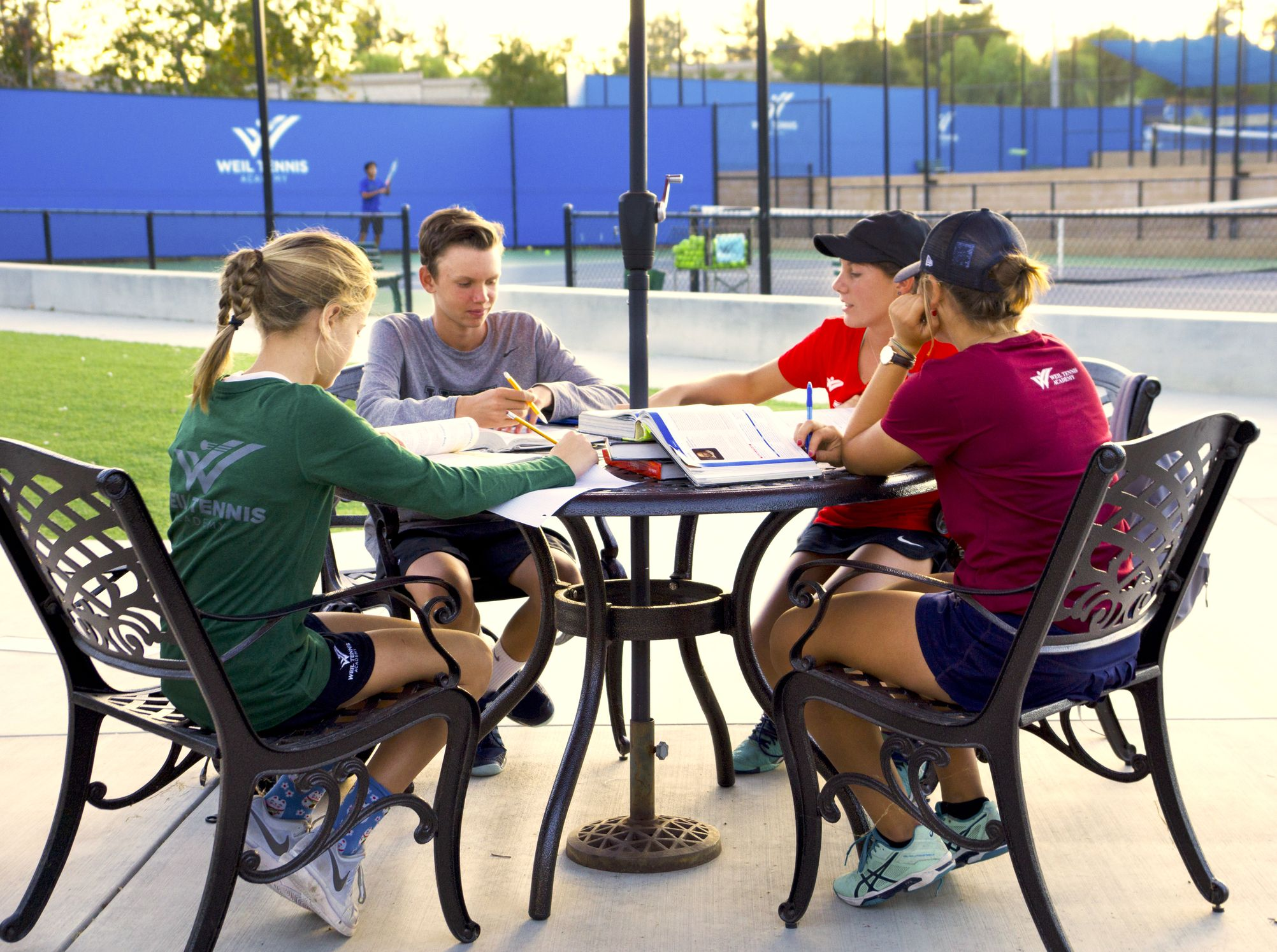 Weil Academy student athletes enjoy study hall outside near the campus tennis courts in Ojai CA near Los Angeles and San Diego.